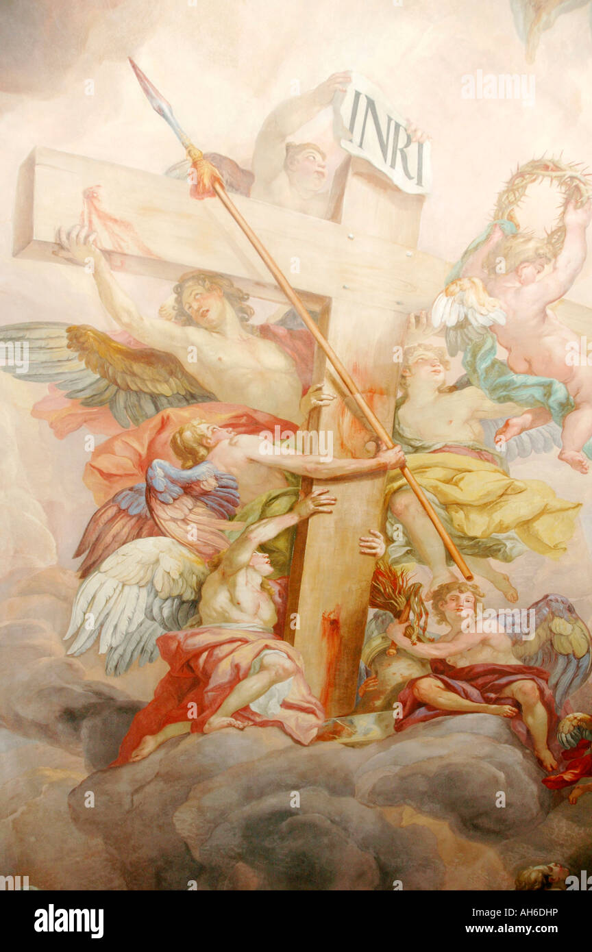 Mural of the cross which jesus was crucified on with angels holding a bloody spear  in St Charles Church in Vienna - Stock Image