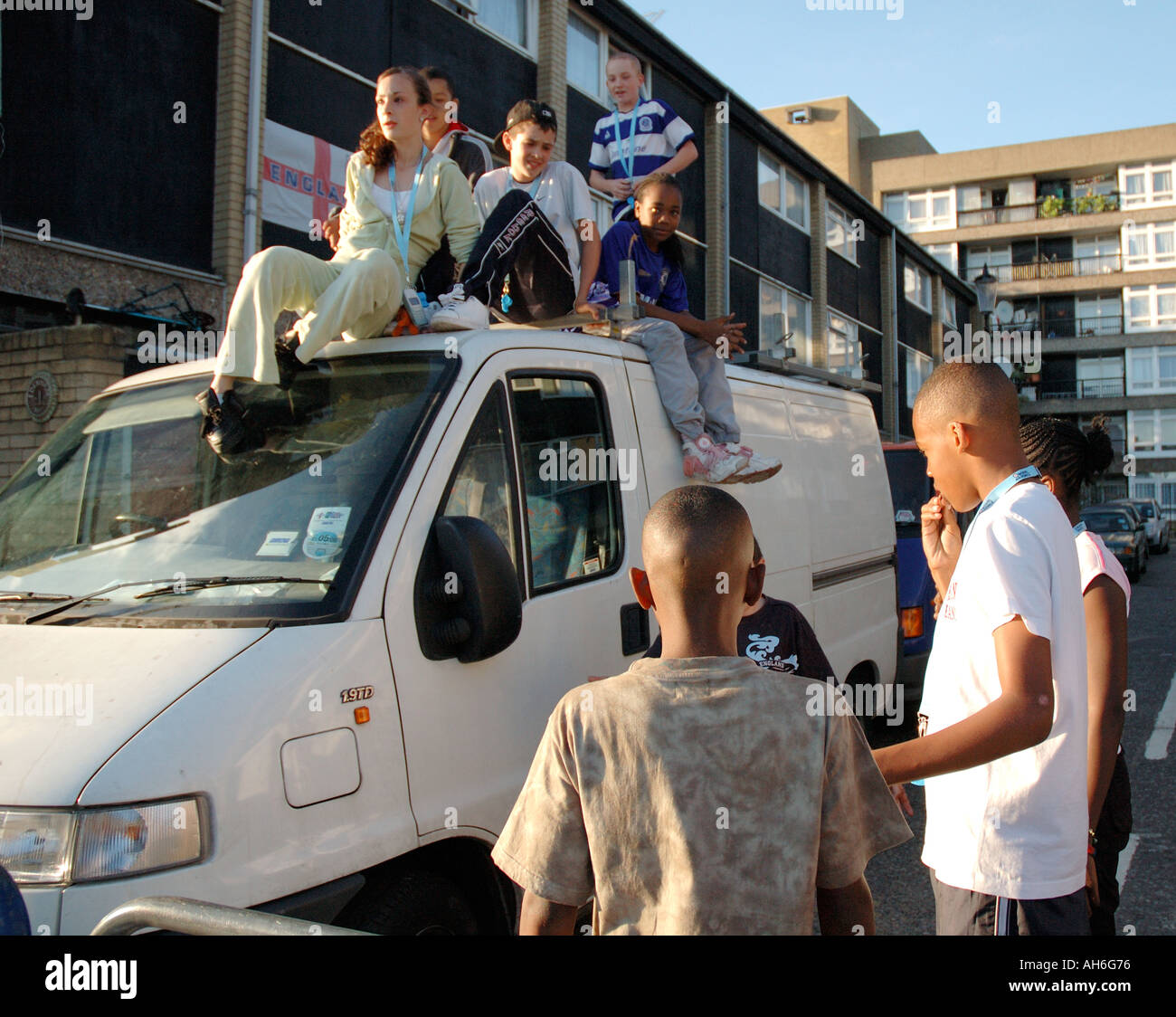 Lively group of children climbing and jumping on van parked on their housing estate in Kensal Green West London. - Stock Image