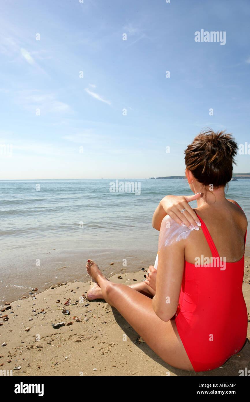 Young Woman Applying Suncream Model Released - Stock Image