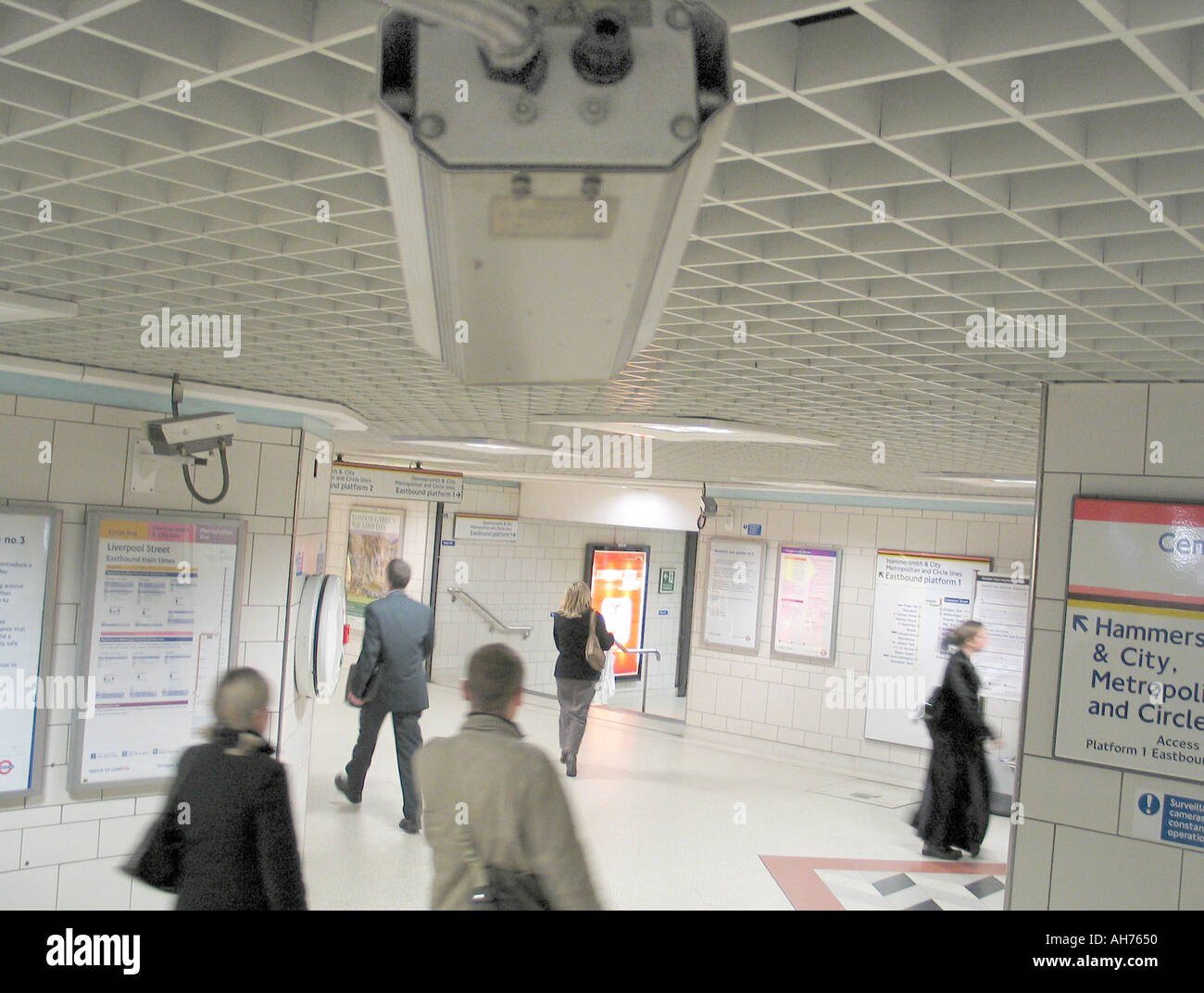 Cctv camera on the London underground with people passing by - Stock Image