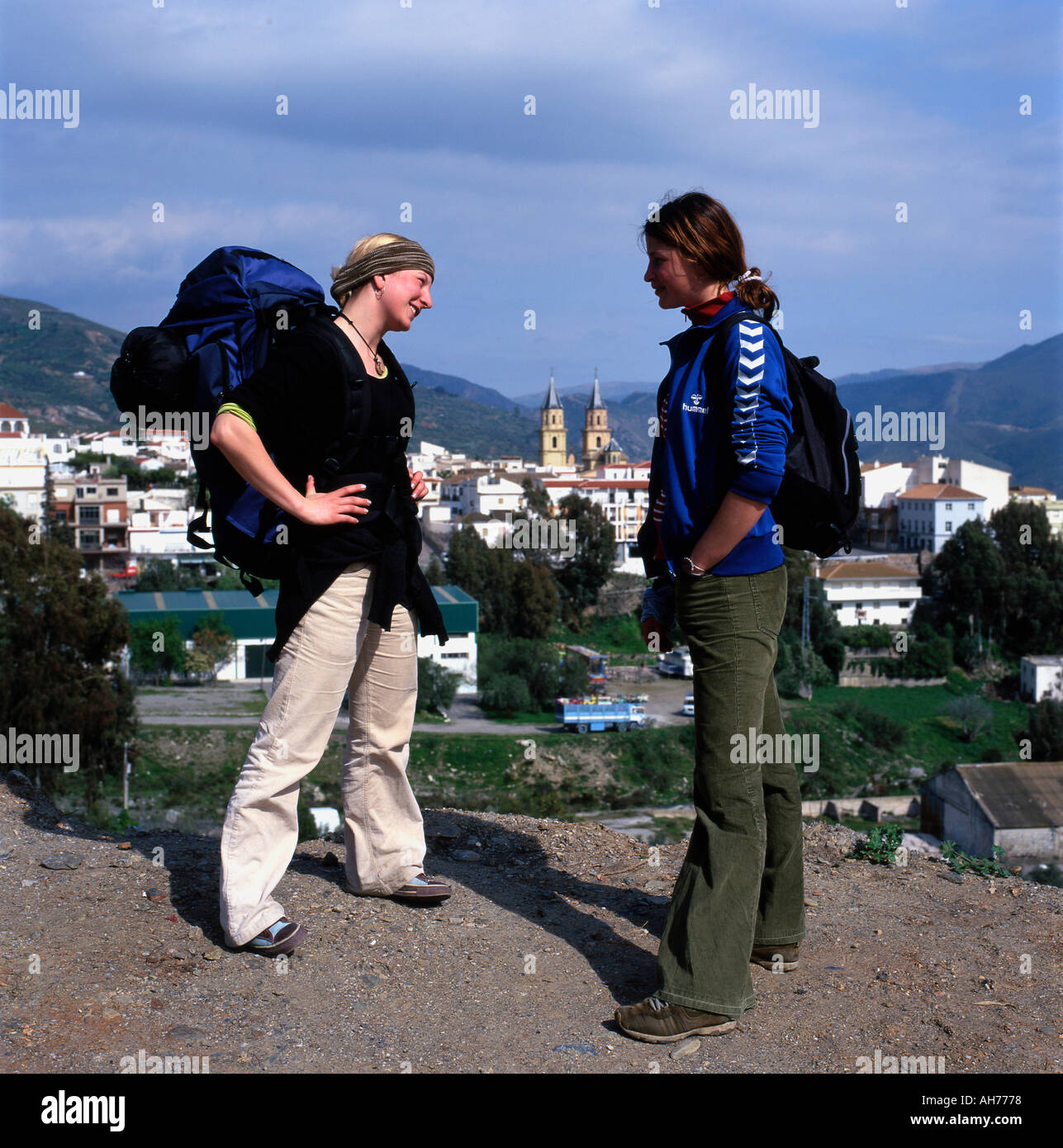 Young female gap year students on holiday with backpack rucksack talking on road above the village of Orjiva in Andalusia Spain KATHY DEWITT - Stock Image