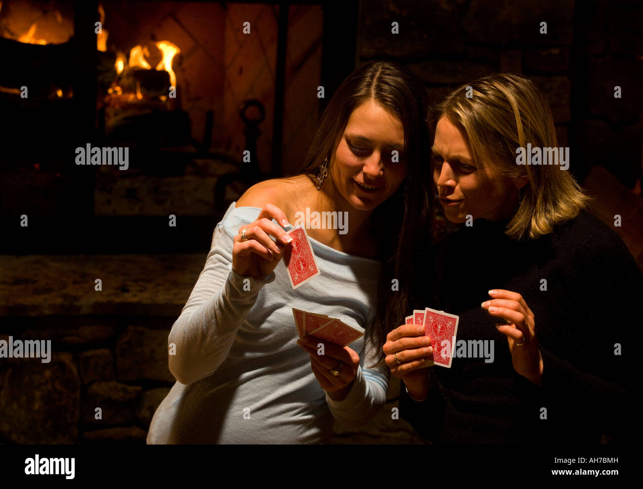 Young woman and a mid adult woman playing cards - Stock Image