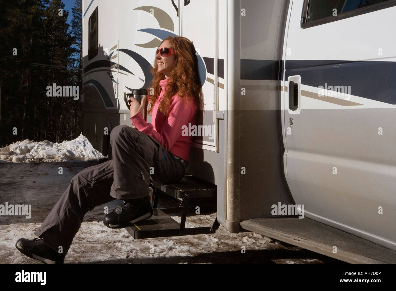 Young woman sitting on the steps of a recreational vehicle - Stock Image