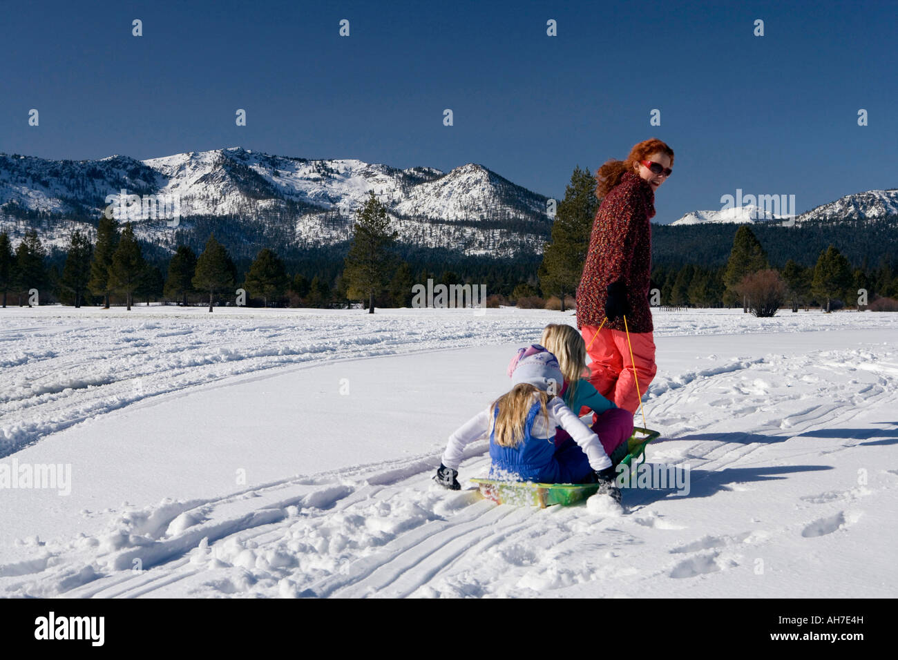 Mature woman pulling her daughters on a sled - Stock Image