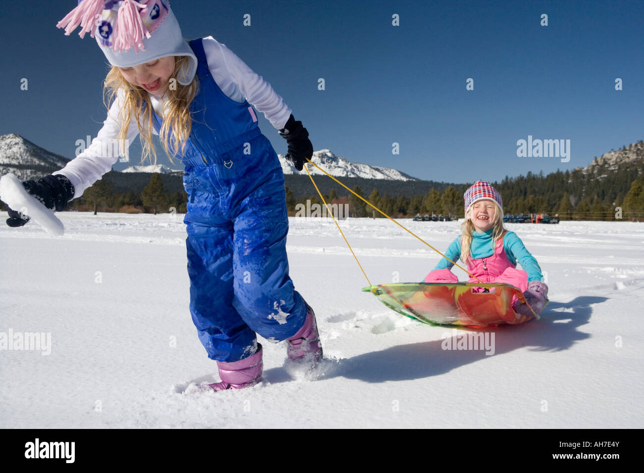 Girl pulling her sister on a sled - Stock Image