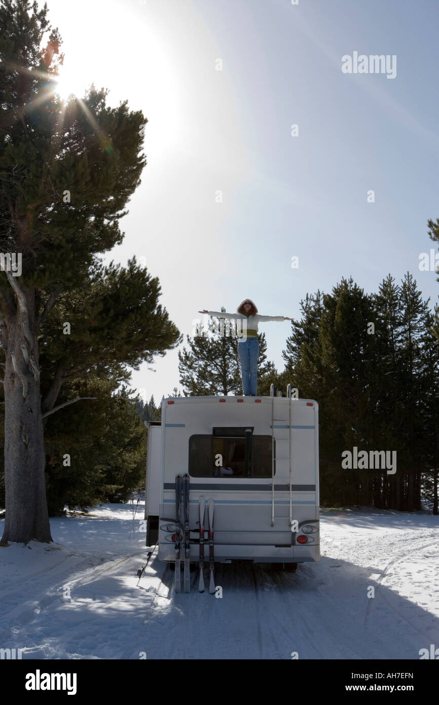 Mature woman standing on top of a recreational vehicle - Stock Image