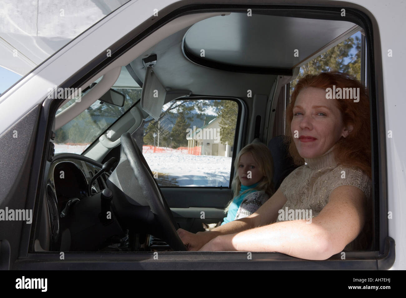 Mature woman driving a recreational vehicle with her daughter sitting beside her - Stock Image