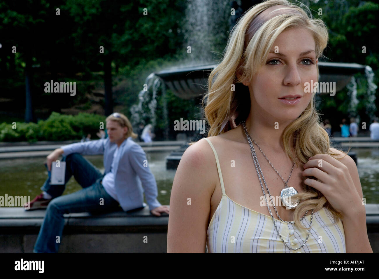 Young woman looking away with a young man sitting in the background near a fountain - Stock Image