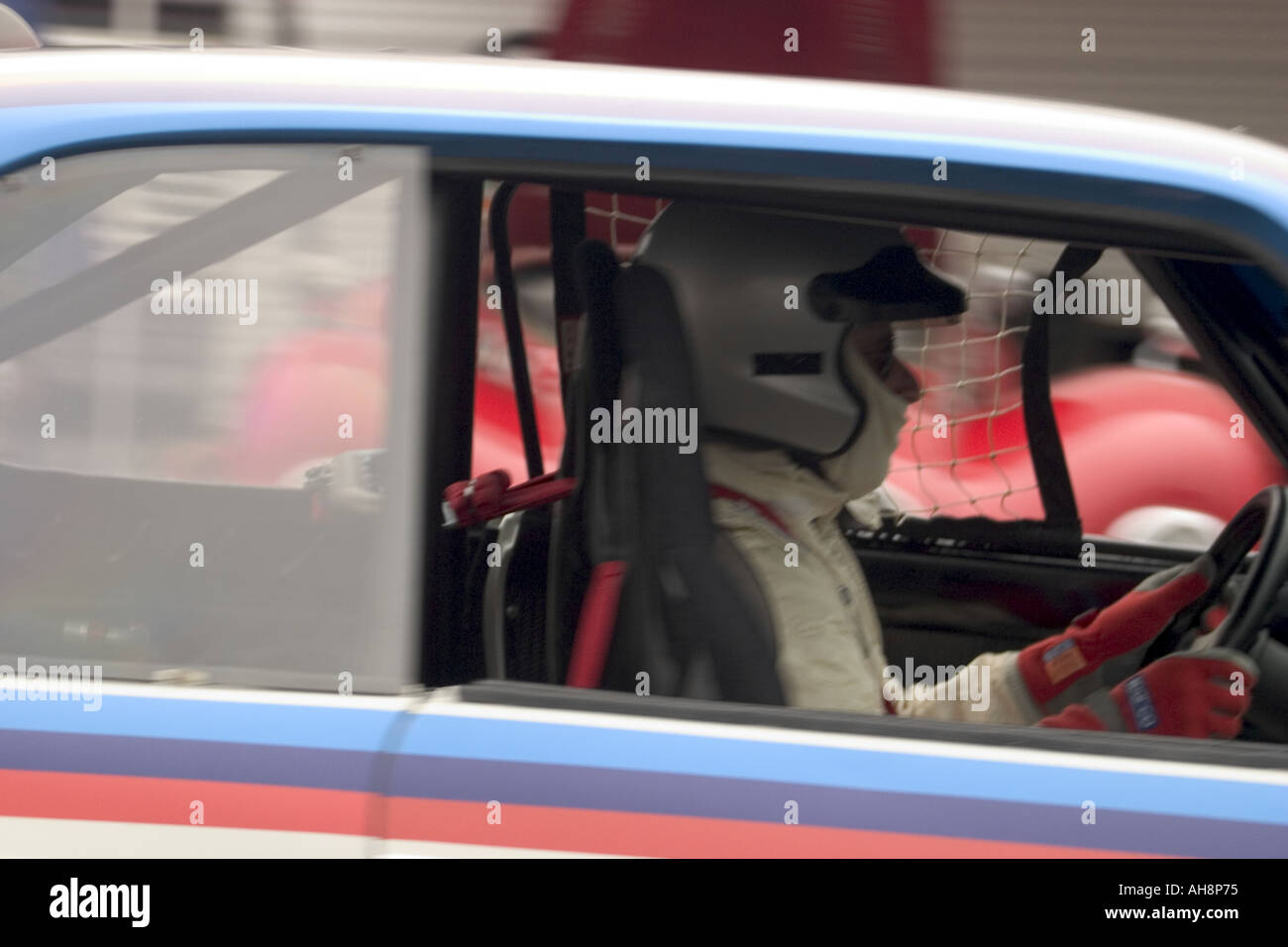 Driver in a Historic Racing Car Driving in the Paddocks - Stock Image