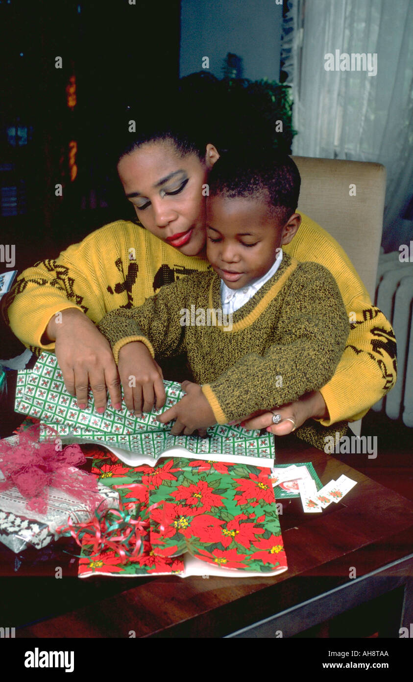 Mother age 38 helping 6 year old son wrap Christmas gifts. St Paul ...