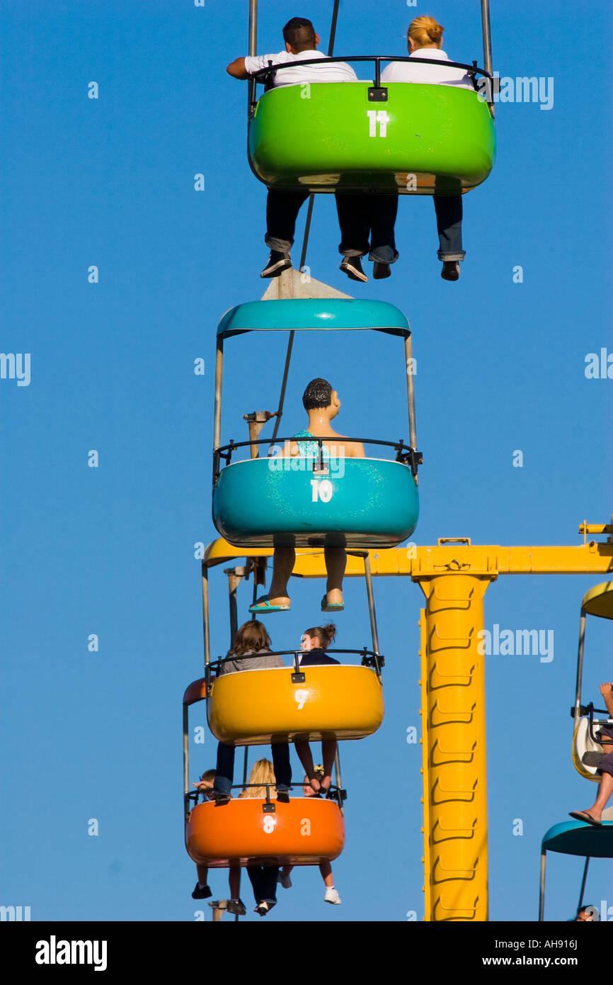 Gondola cars in primary colors moving across the sky with passengers legs dangling below at Santa Cruz Boardwalk - Stock Image