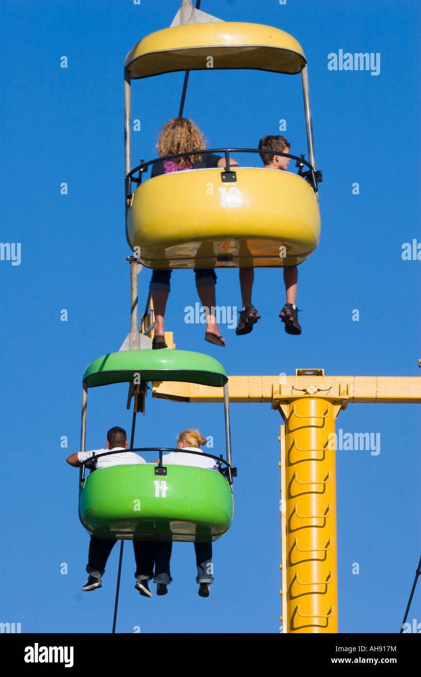 Two colorful gondola cars moving across the sky with passenger s legs dangling below at Santa Cruz Boardwalk amusement - Stock Image