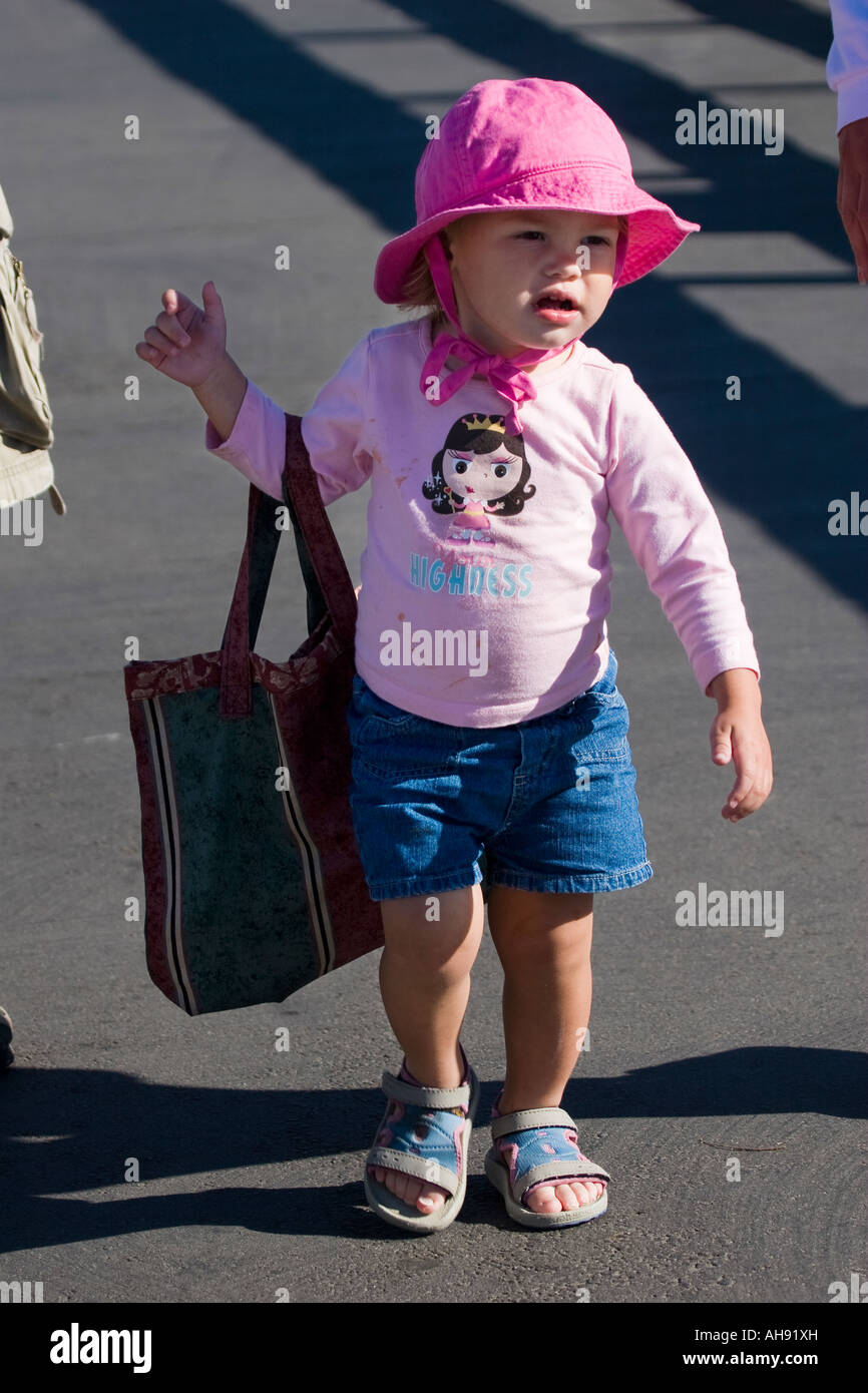 Toddler girl in a pink outfit walking while holding a bag that is too big for her, playing grownup in carrying her - Stock Image