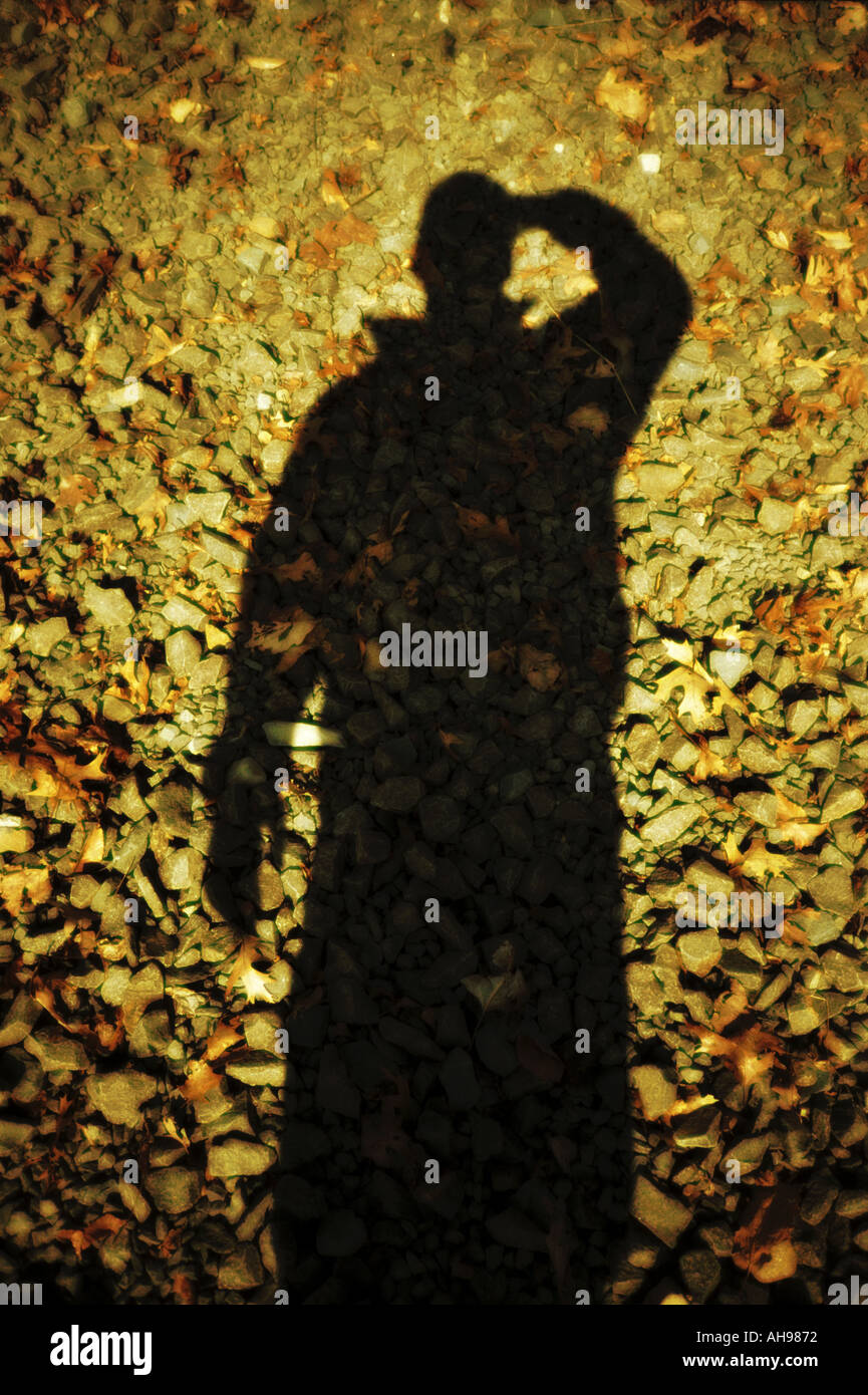 Photographer taking self portrait with shadow - Stock Image