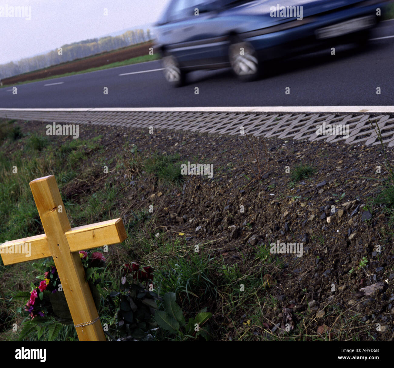 cross for the victims of traffic on the border of a country road - Stock Image