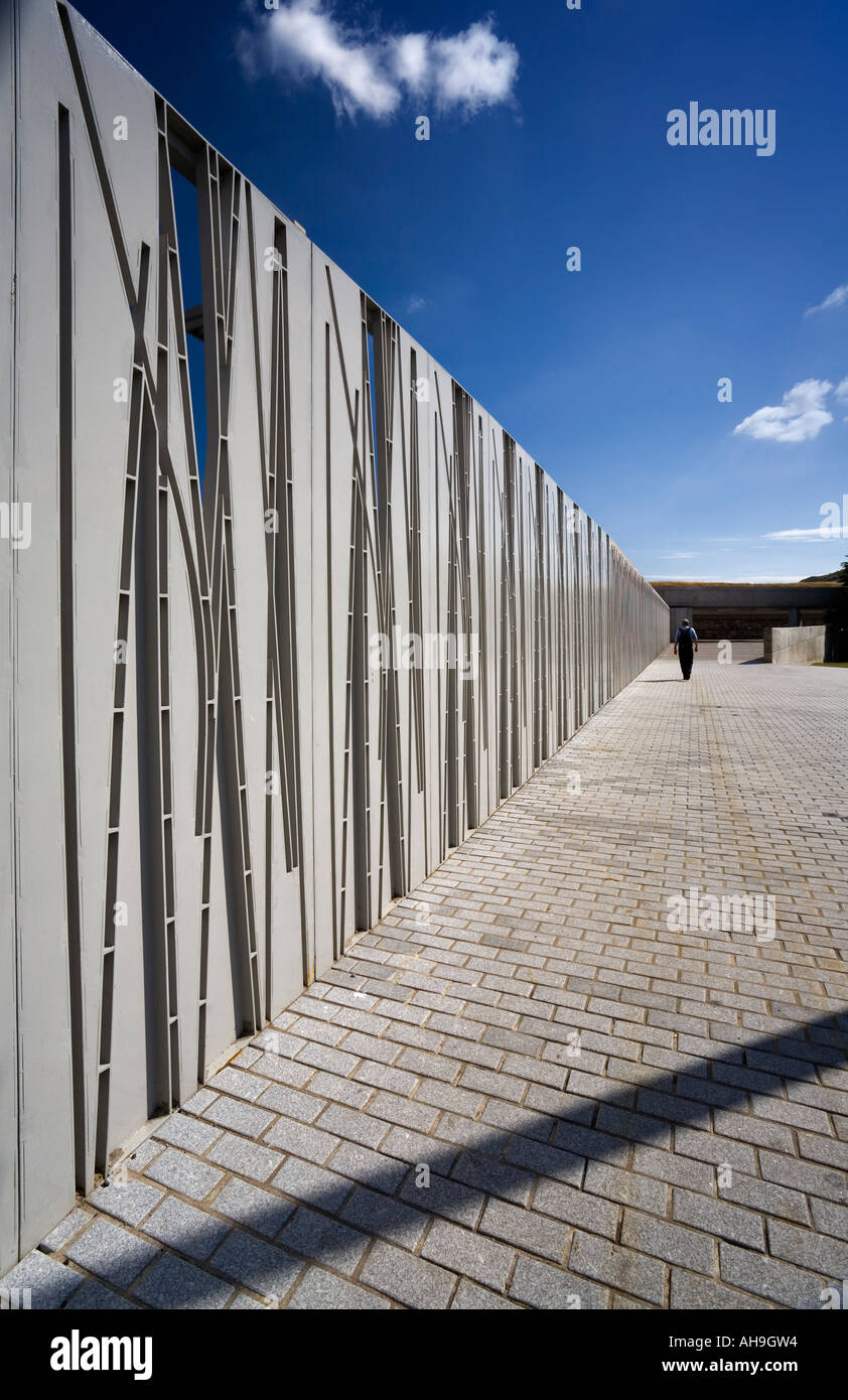Lone walker beside the stylised security fencing at the Scottish Parliament - Stock Image