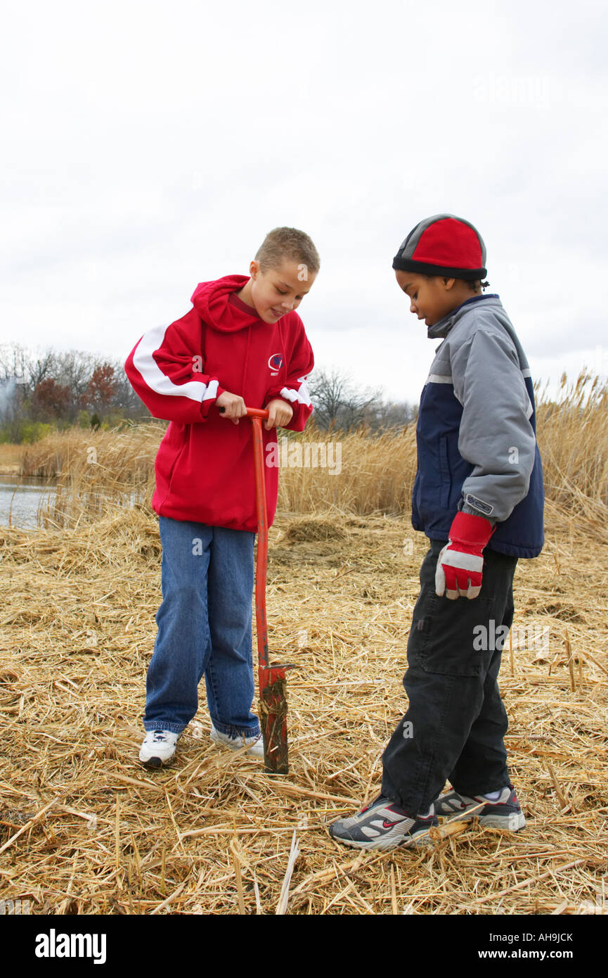 ILLINOIS Vernon Hills Two boys use spade to prepare hole for tree