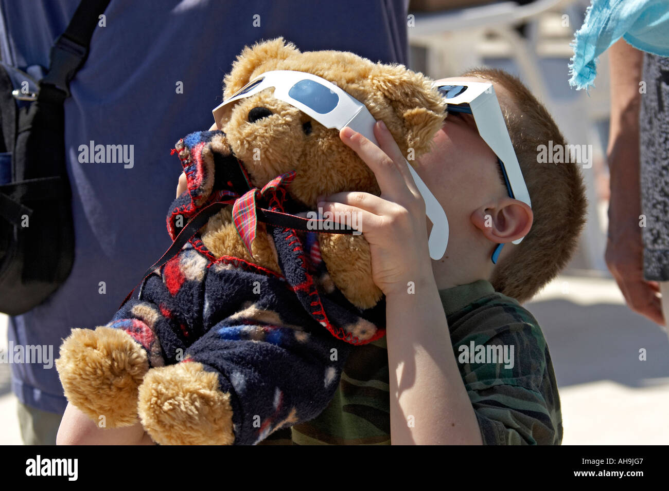 Young boy with teddy bear and solar viewer safety glasses watching the initial stages of the Total Eclipse of the Stock Photo