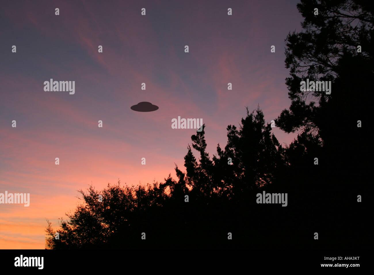 UFO silhouette against sunrise - Stock Image