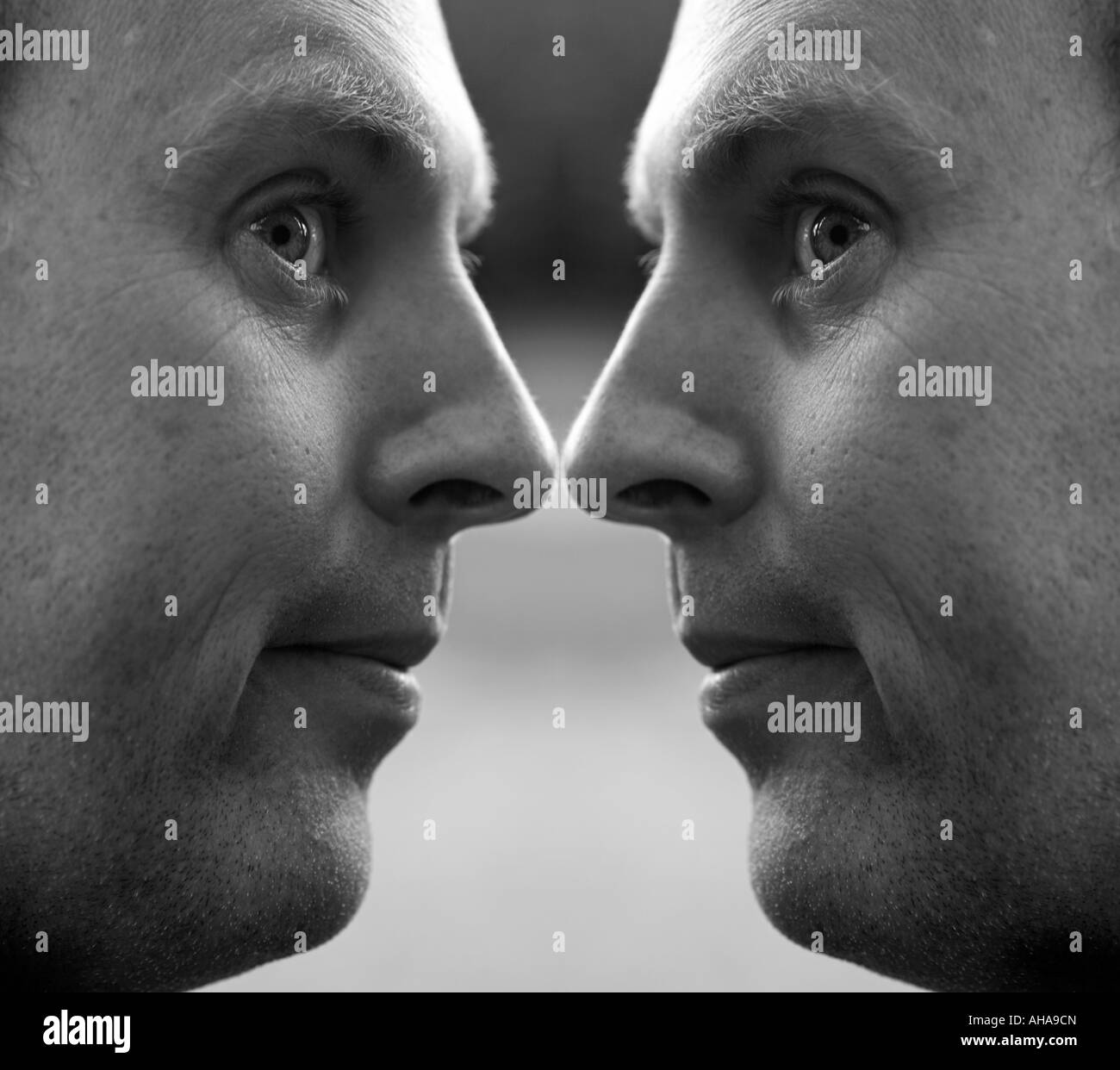 Black and white image of a mans face duplicated as a mirror image. - Stock Image