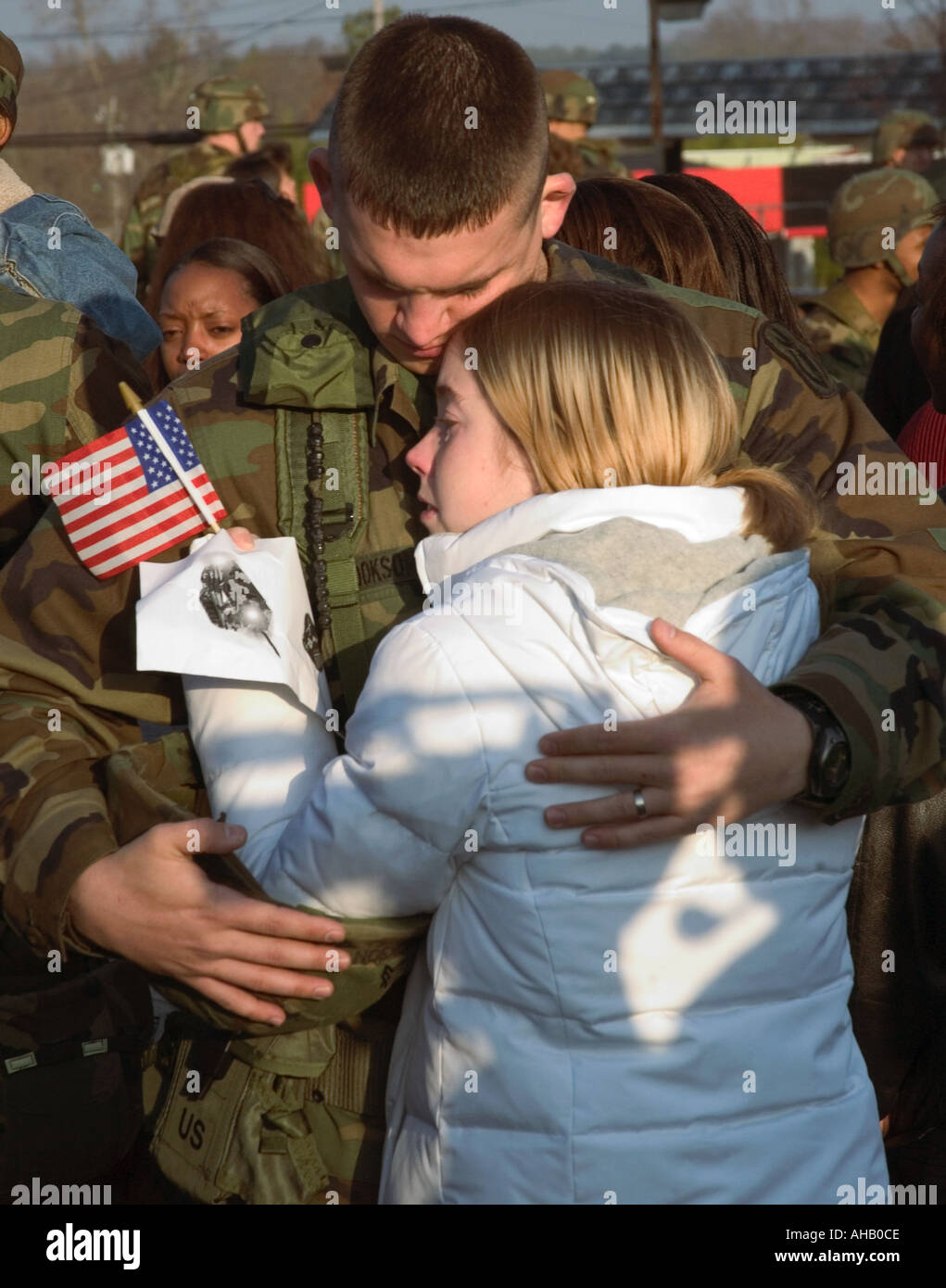 Soldier 20 to 24 Leaving for Deployment to Iraq Hugs His Wife Holding US Flag USA - Stock Image