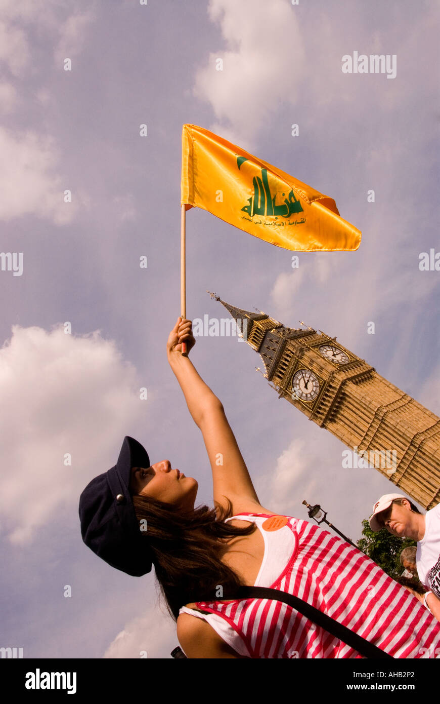 Young Muslim protester wielding yellow flag of Hizbollah during Stop the War s march and demo against israeli agression - Stock Image