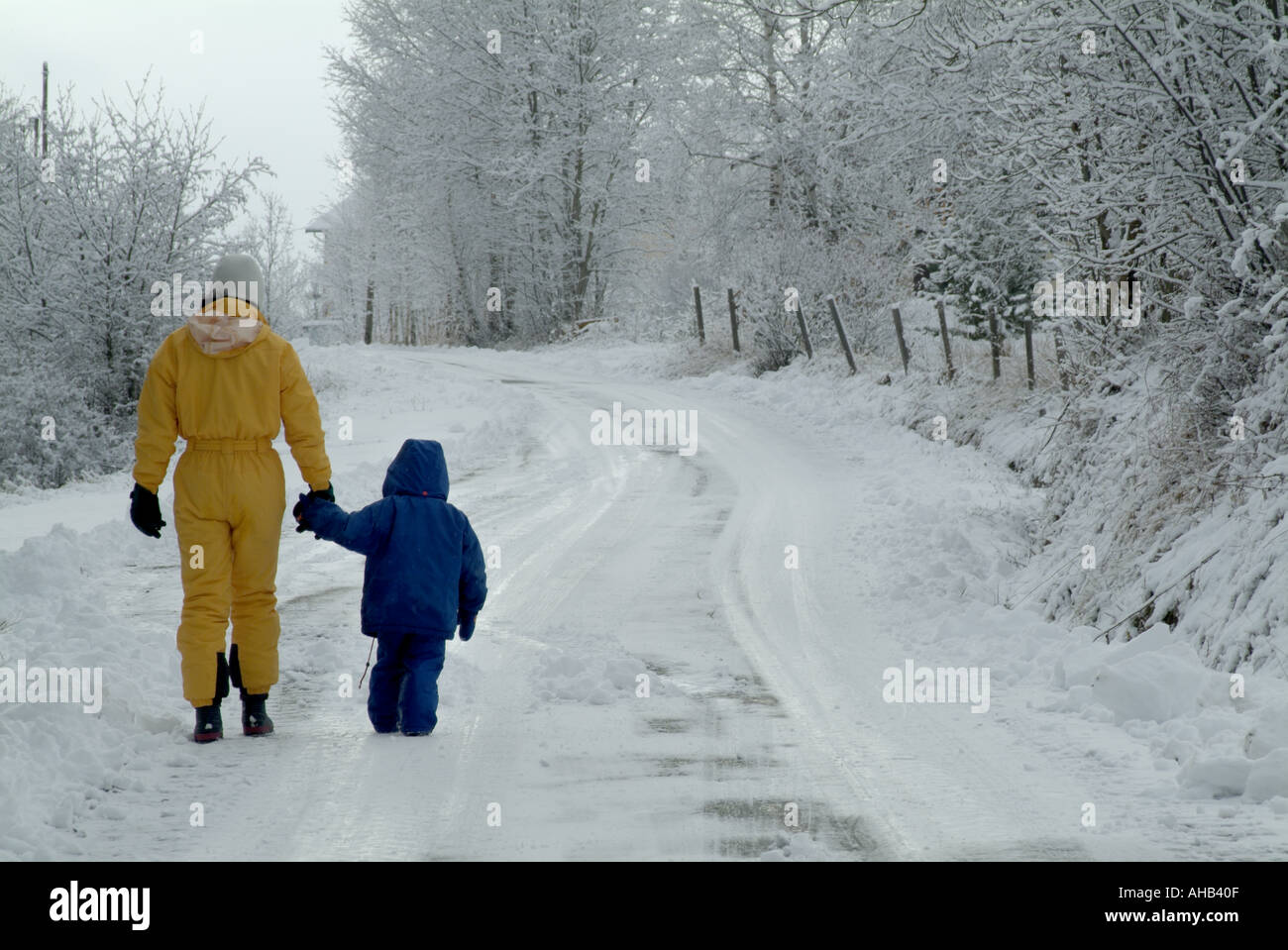 Mother and her three year old daughter walking along a snowy road, Selonnet, French Alps, France. Stock Photo