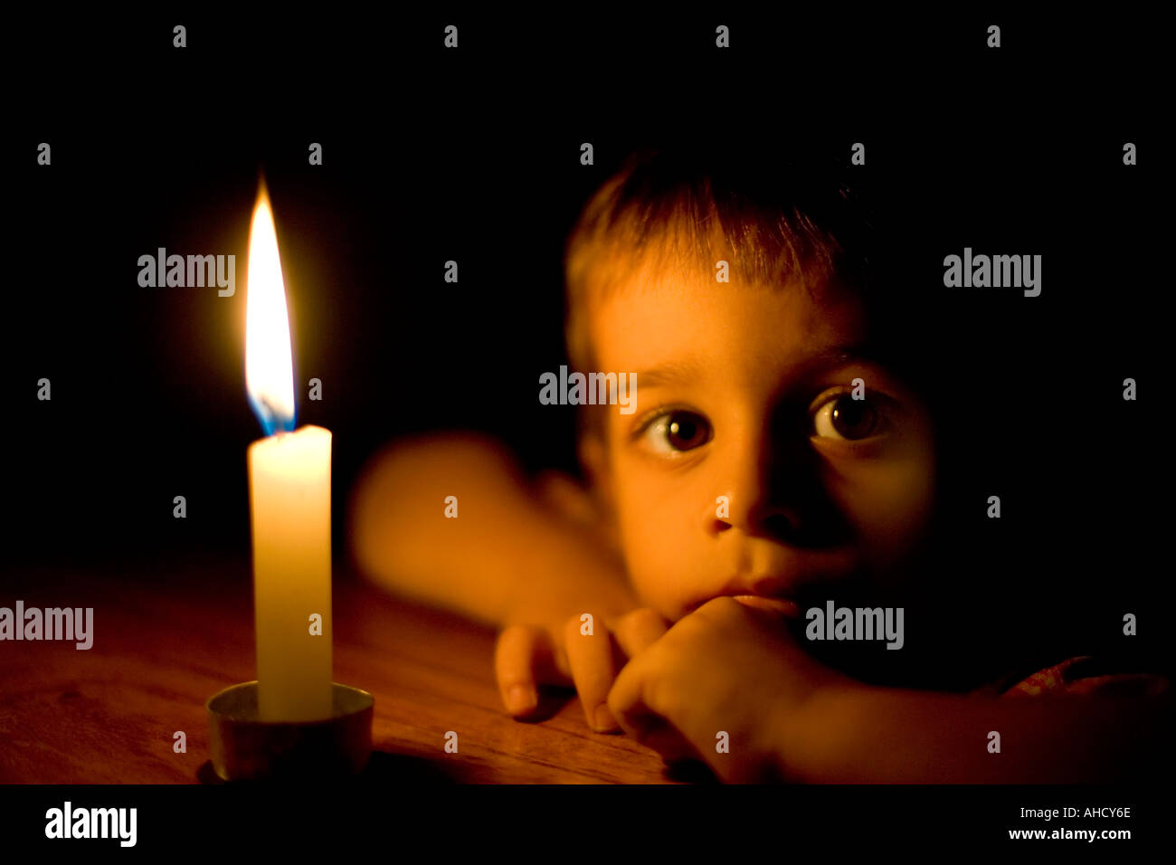 Head and shoulders portrait of a small boy in candlelight - Stock Image