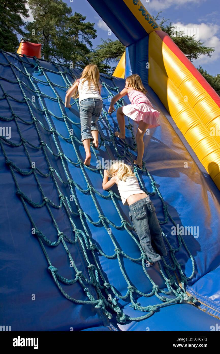 Girls climbing rope ladders on Velcro Olympics Eastnor Fund Day near Malvern UK - Stock Image