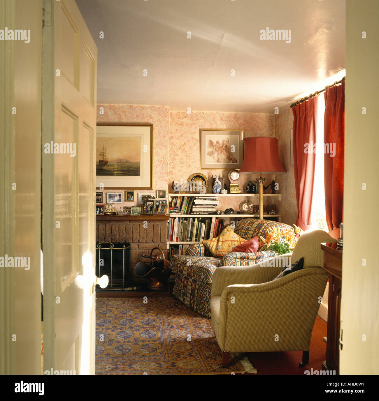 Door Open To Old Fashioned Living Room With Patterned Carpet And Wallpaper  And Cream Armchair
