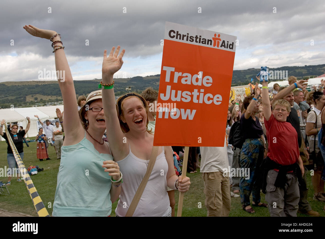 Two young women wave Christian Aid Trade Justice Now placards at Make Poverty History demonstration Greenbelt 2005 UK - Stock Image