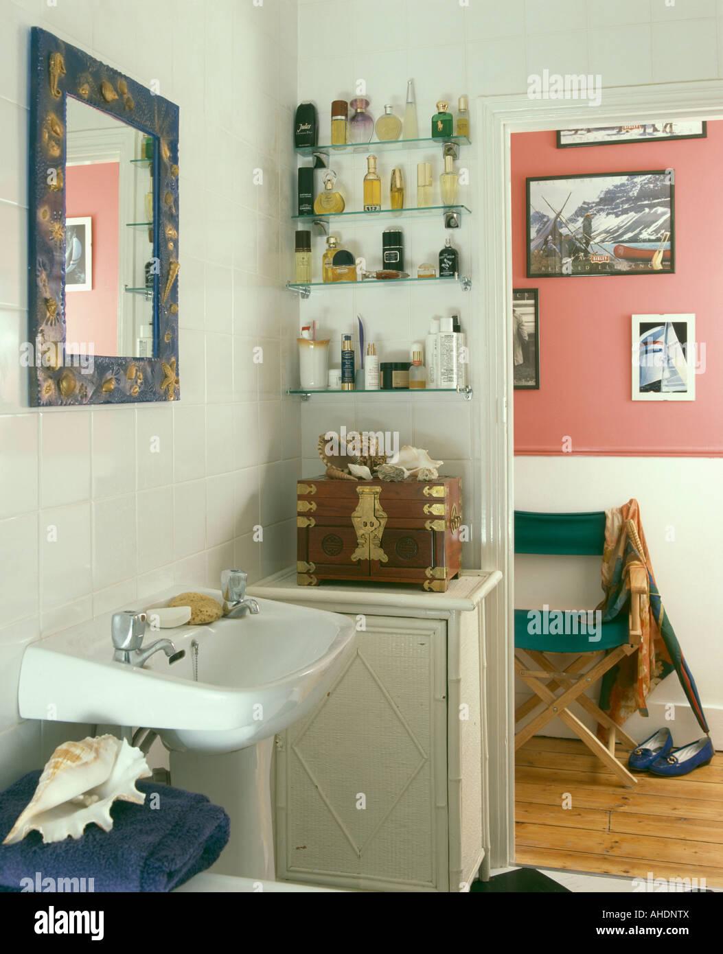 Perfume bottles on glass shelves beside open door in small white ...