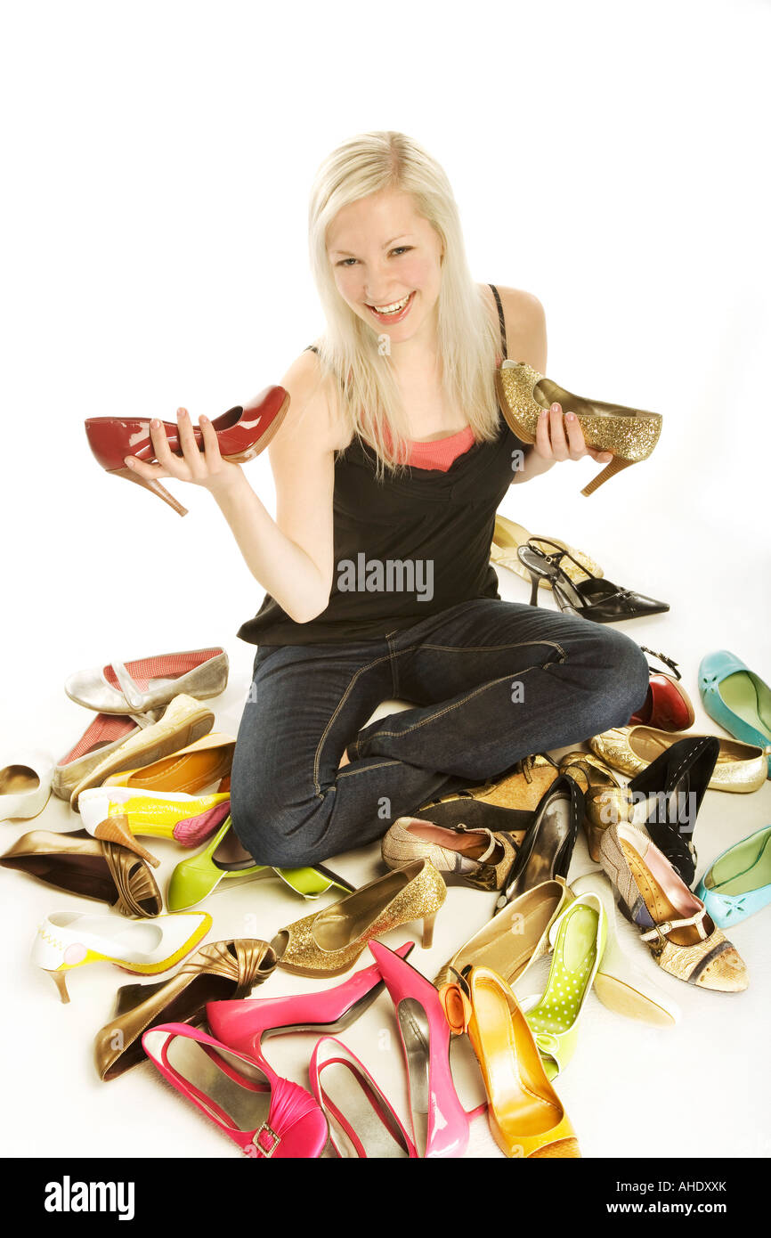 Woman sitting in midst of pile of shoes holding two high heeled shoes - Stock Image