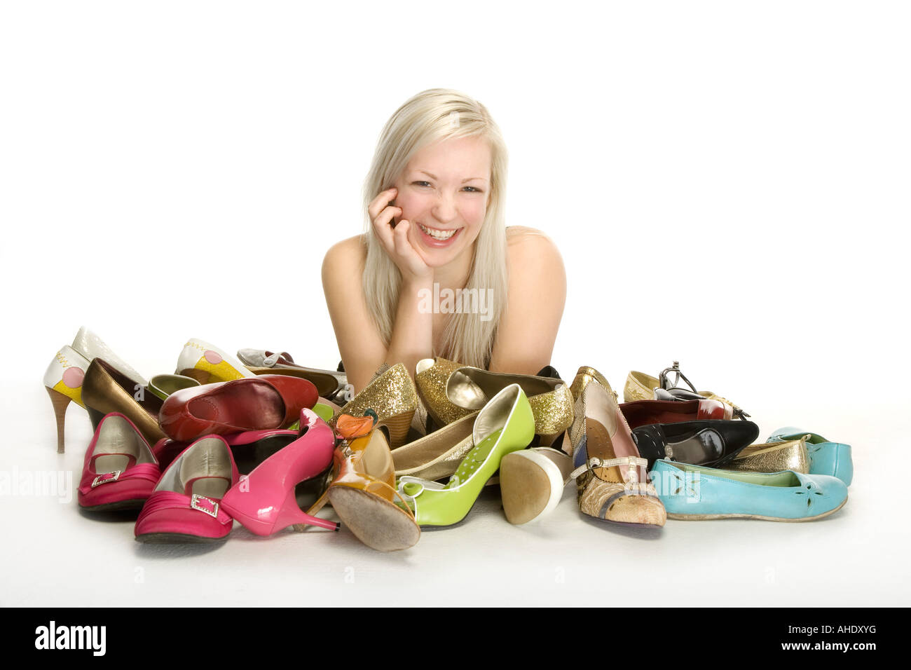 Woman smiling with pile of shoes in front of her - Stock Image