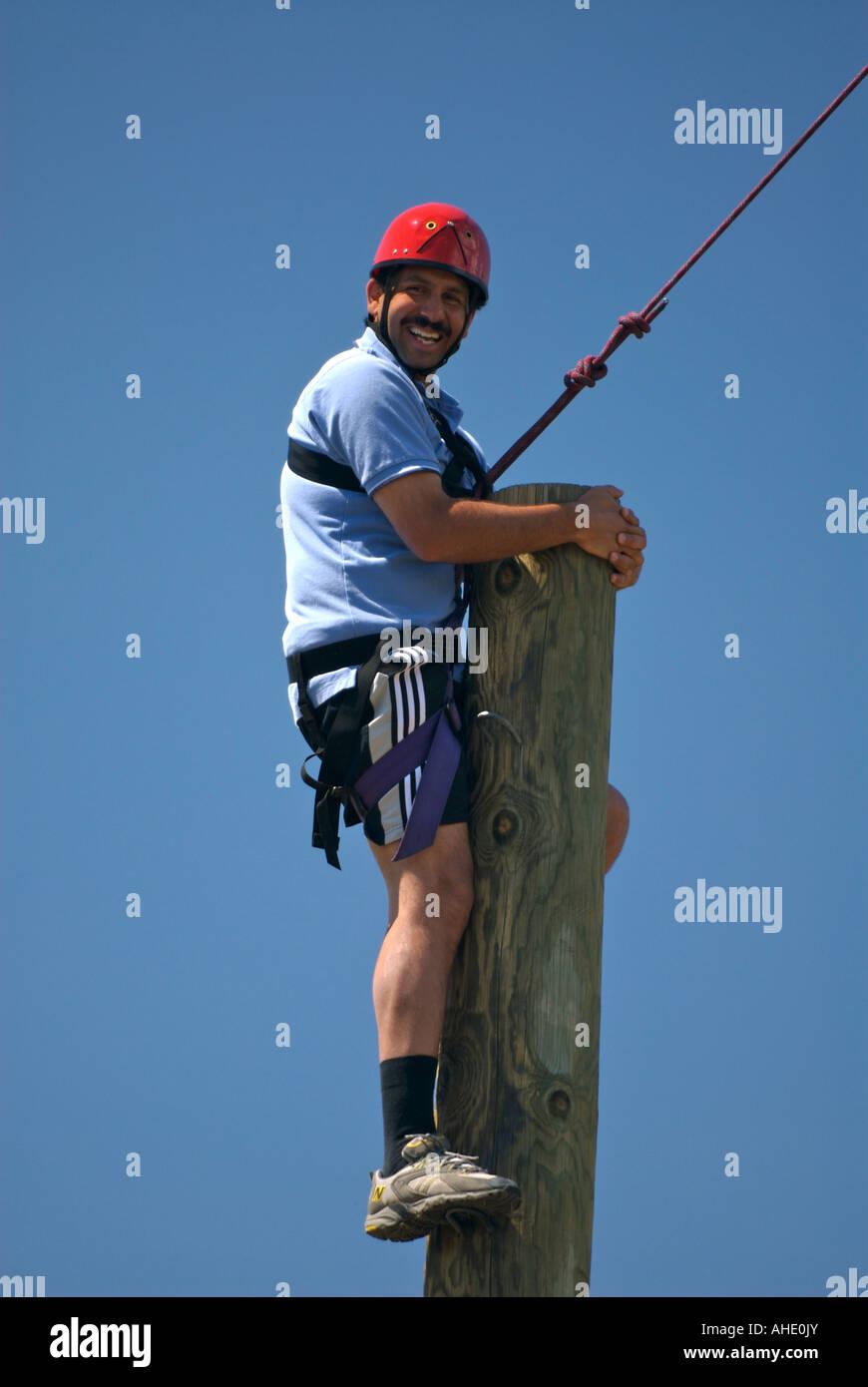 A smiling Pakistani man hugs a telephone pole as he climbs to the top - Stock Image