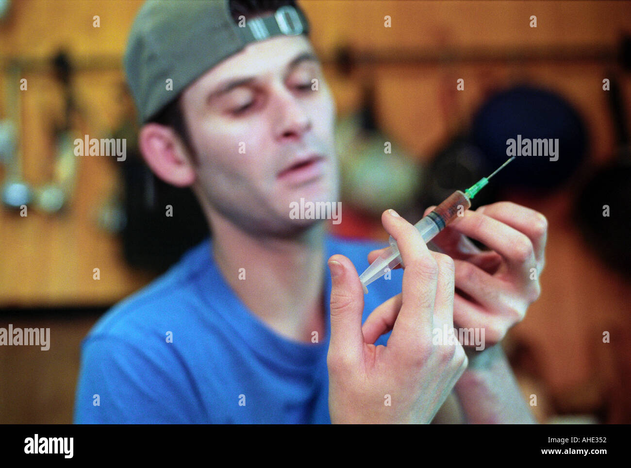 Heroin addict preparing to inject heroin. - Stock Image