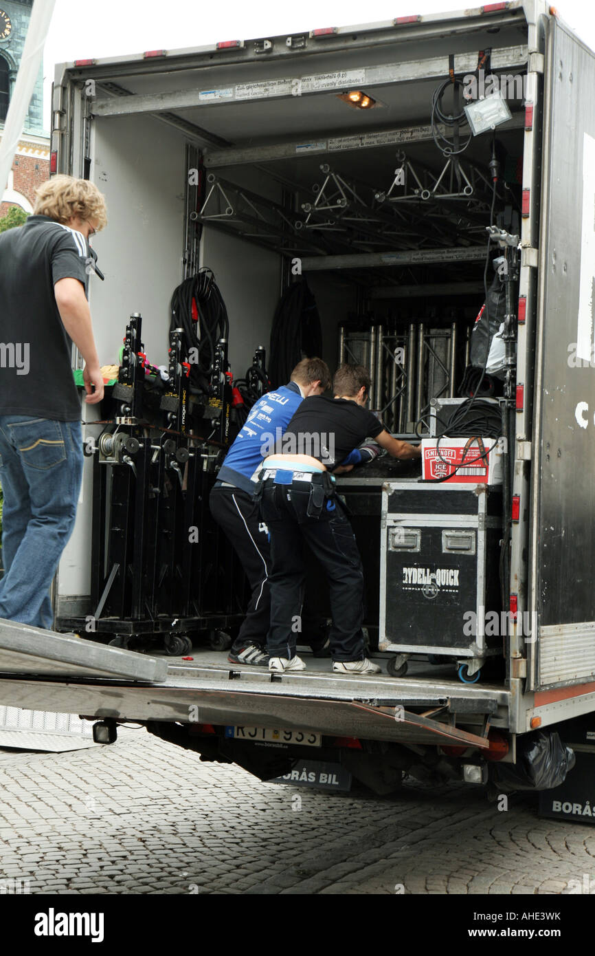 Roadies unloading a truck with gear for a rock concert - Stock Image