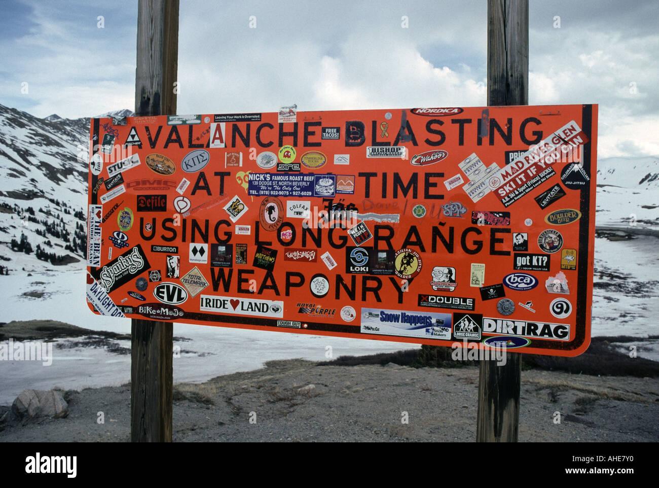 Avalanche blasting warning signpost with graffitti stickers Loveland Pass Highway 6 Colorado USA - Stock Image