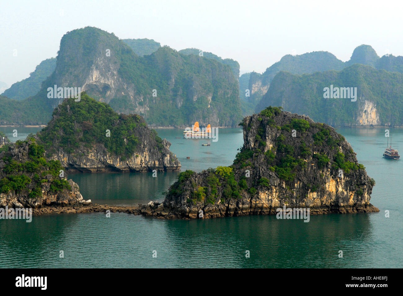 Vietnam , Halong Bay , panoramic view over limestone islands & lagoon with junk boats & cruise ships passing - Stock Image
