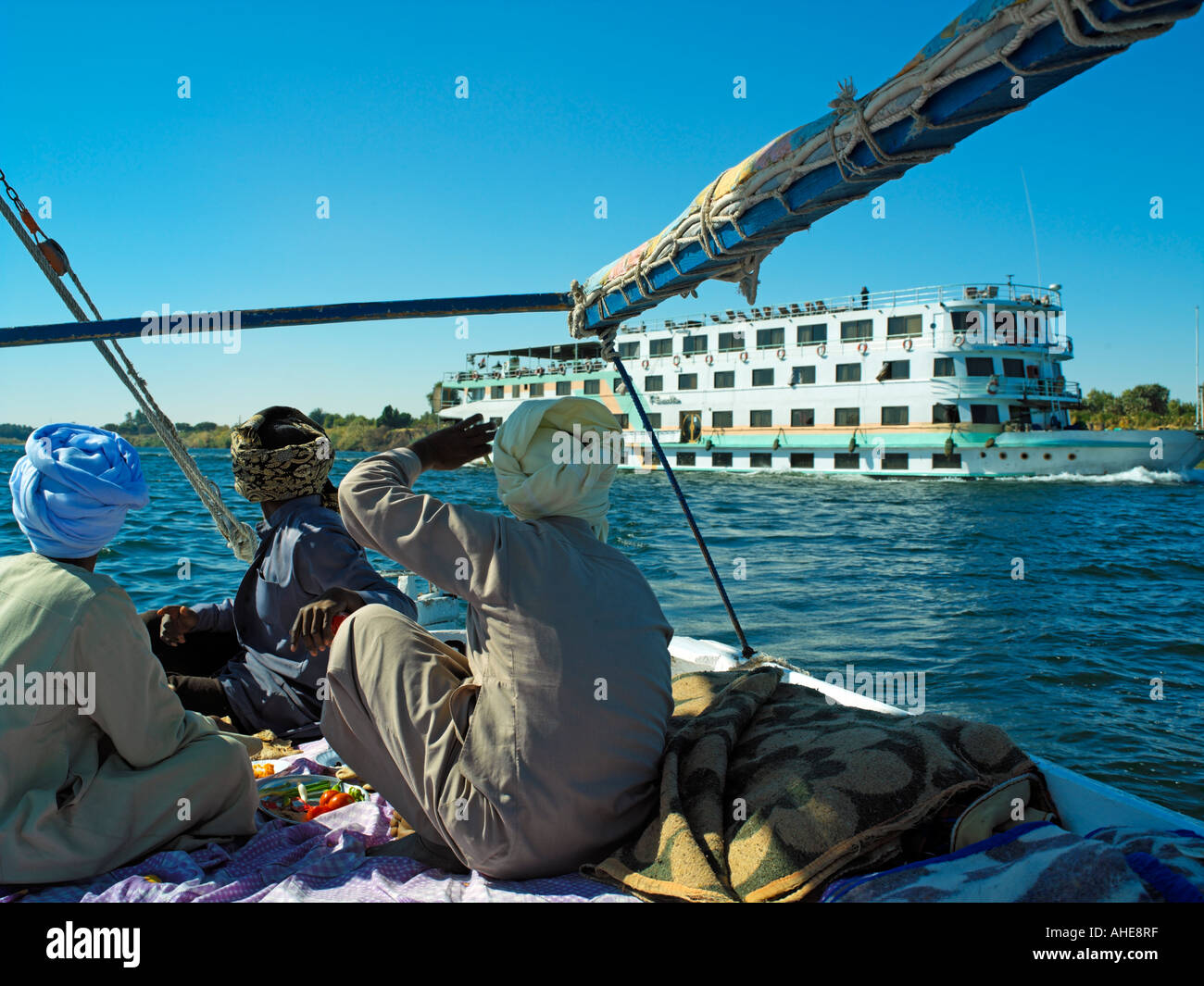 Felucca boatmen taking lunch as a Nile Cruiser heads downriver - Stock Image