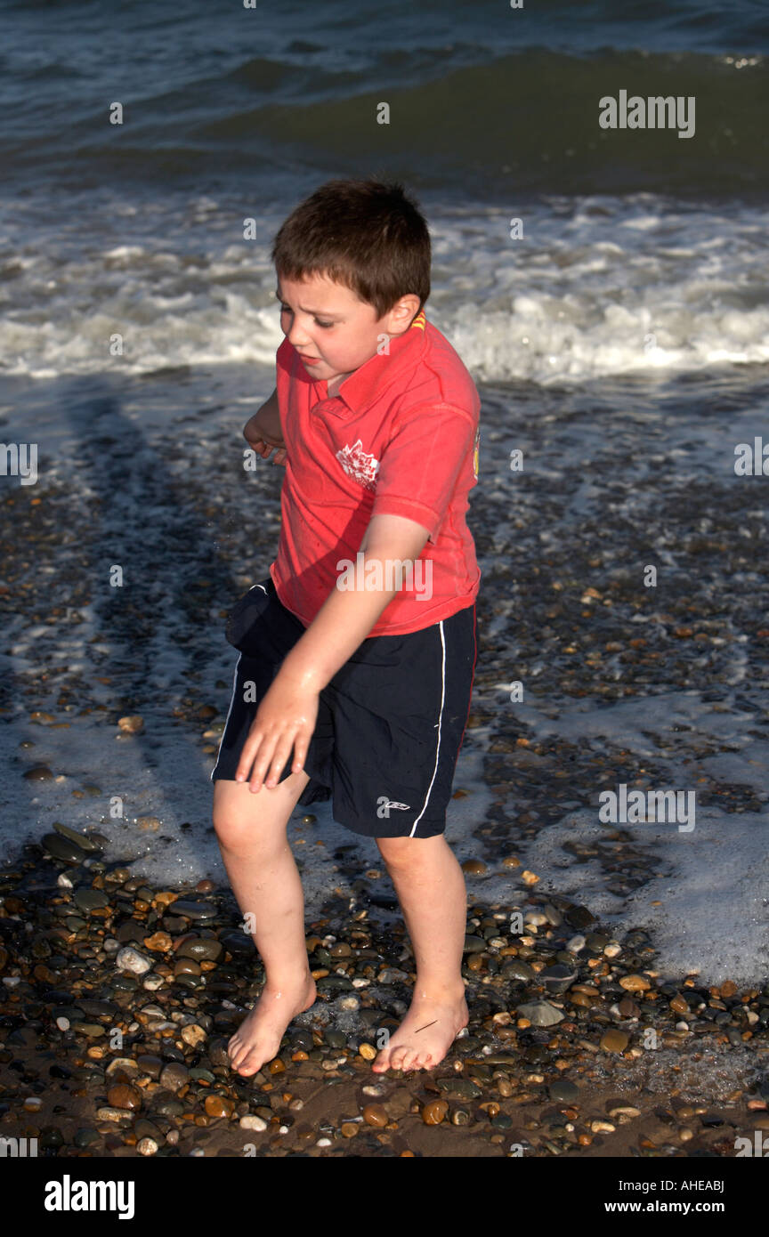 young seven year old boy tip toeing out of cold wet sea while playing on the beach in county wexford republic of - Stock Image