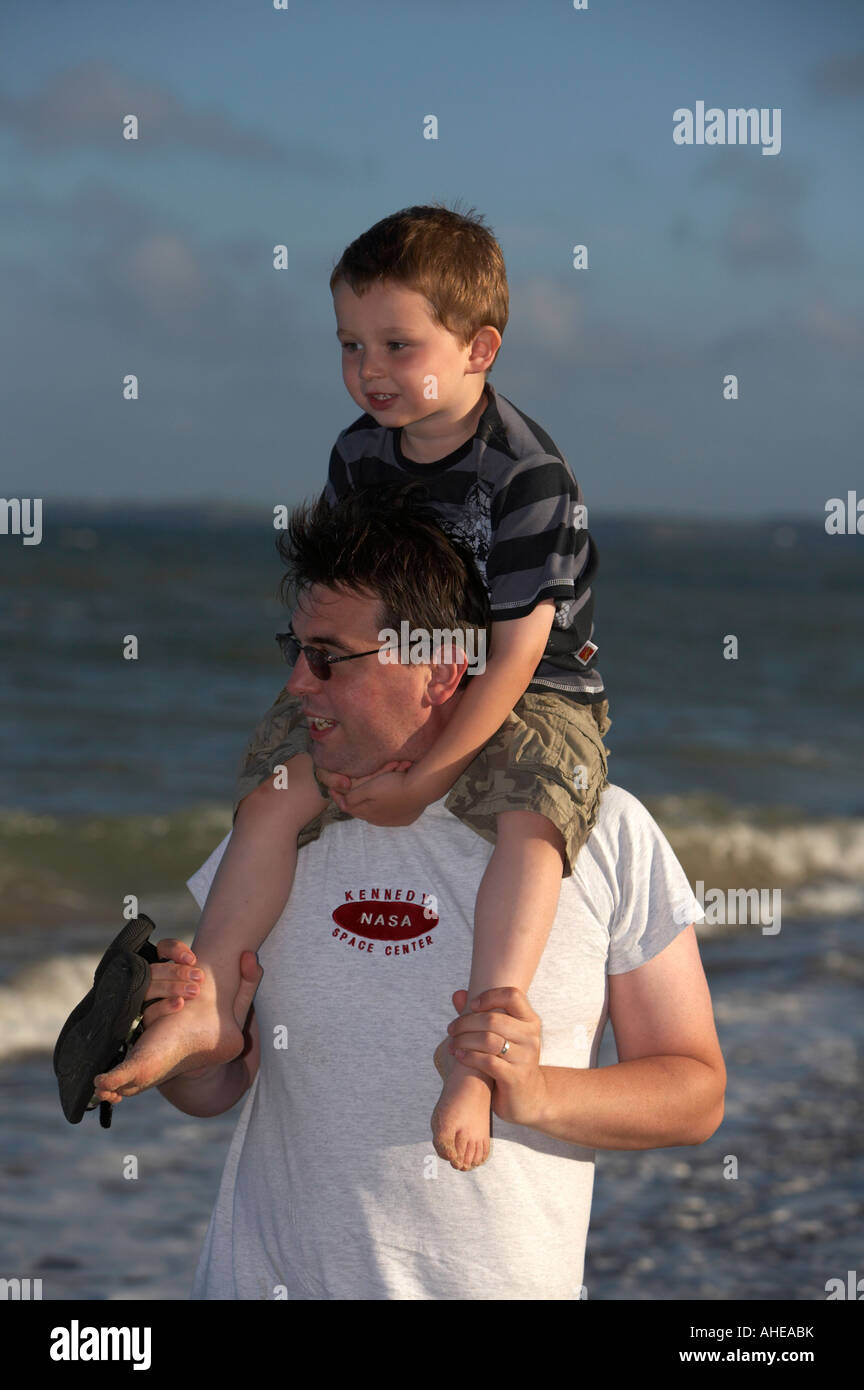 mid thirties dad wearing sunglasses carrying three year old son on his shoulders whilst walking on the beach in Stock Photo
