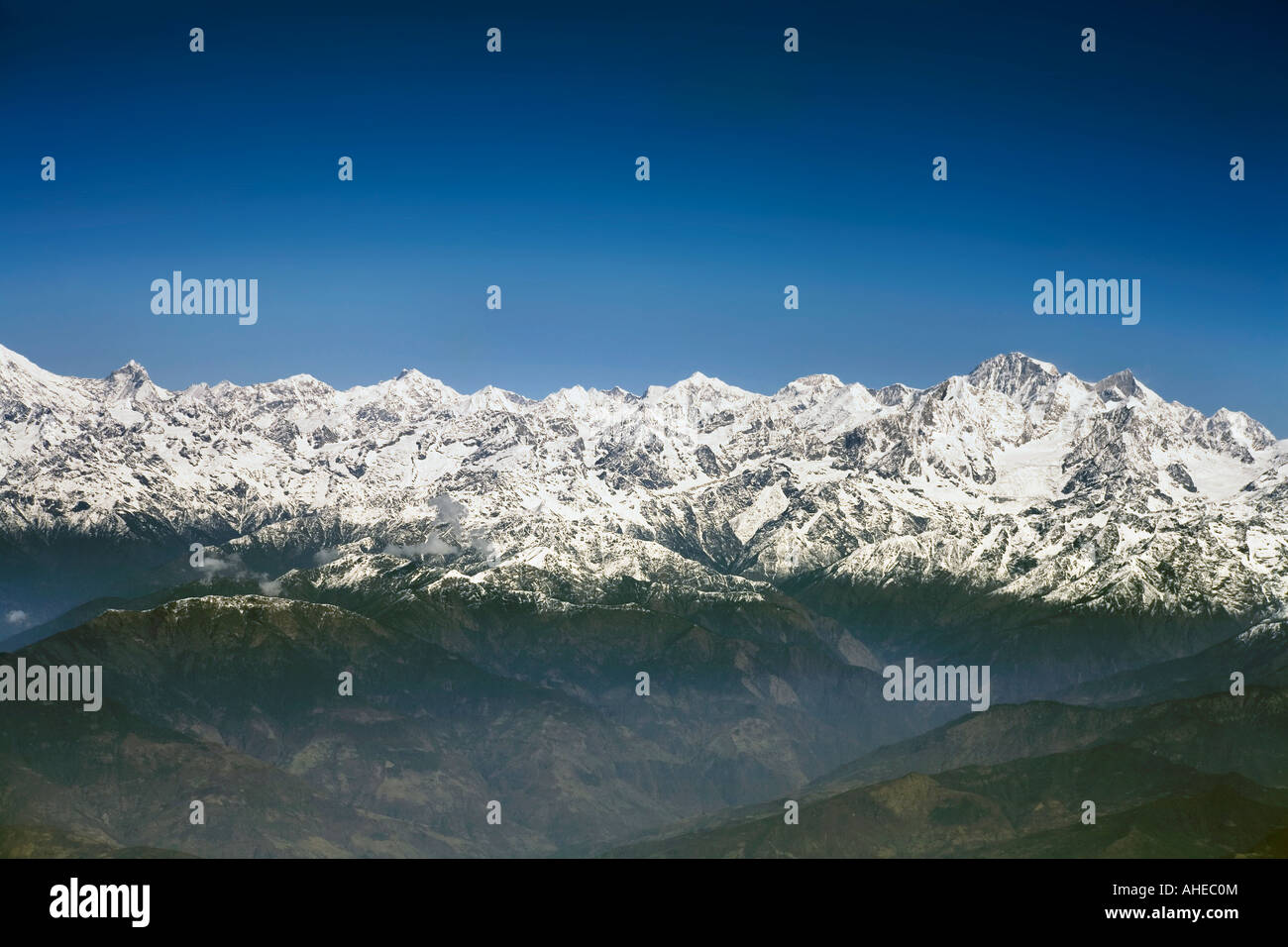 Wide expansive aerial view of Snowcapped Himalayan peaks over their foothills below a clear blue sky Stock Photo