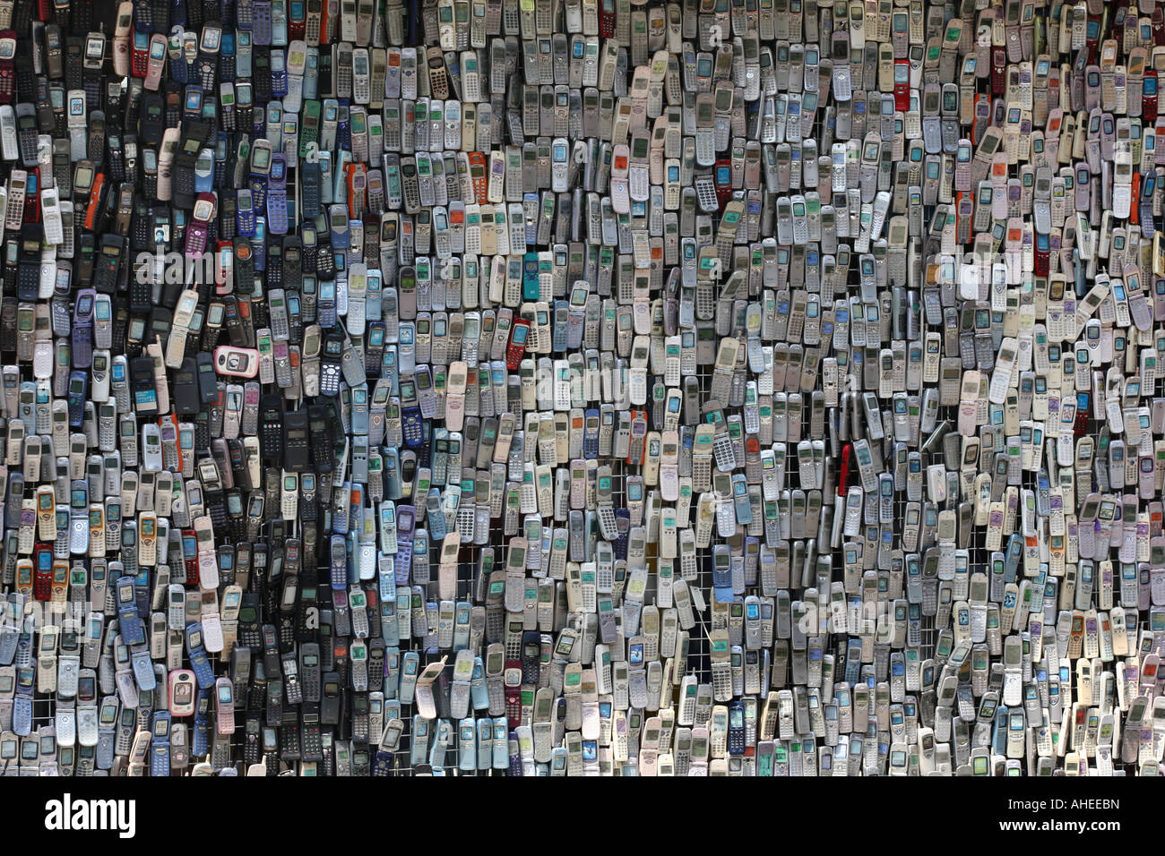 Wall of mobile phones on the exterior of mobile telephone shop in Tokyo Japan - Stock Image