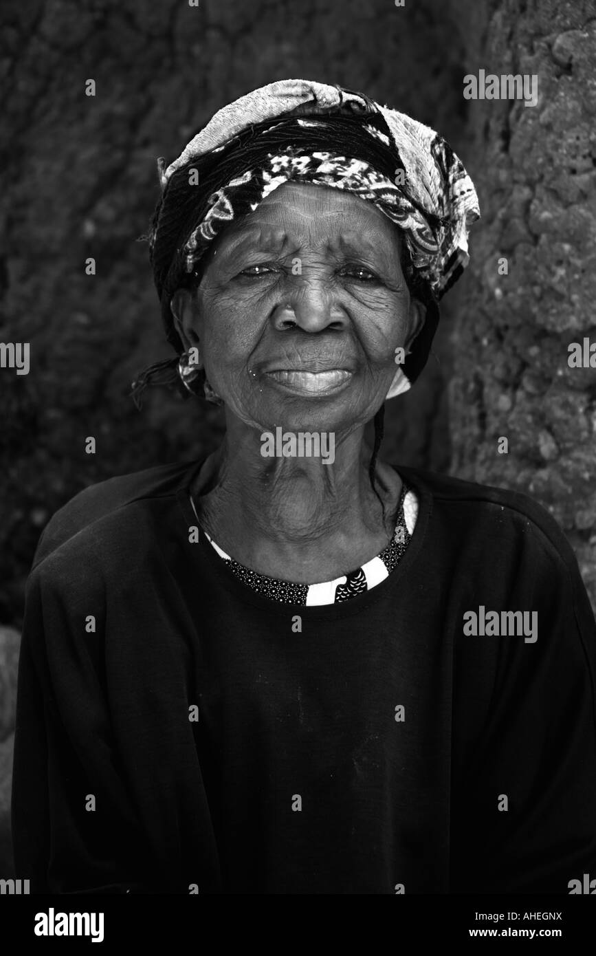 Senior African woman with head wrapped in scarf staring and contemplating. - Stock Image