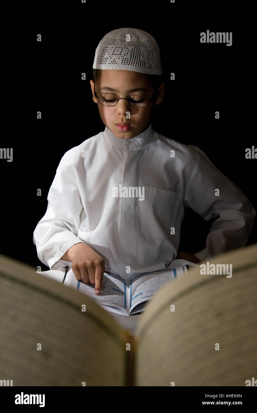 A young boy reading the Qur'an - Stock Image