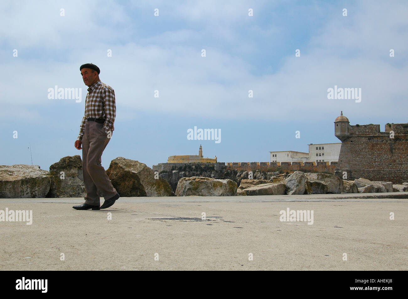 An elderly Portuguese man walking along the pier of the old harbor in Peniche a seaside city located in Oeste Subregion in Portugal. - Stock Image