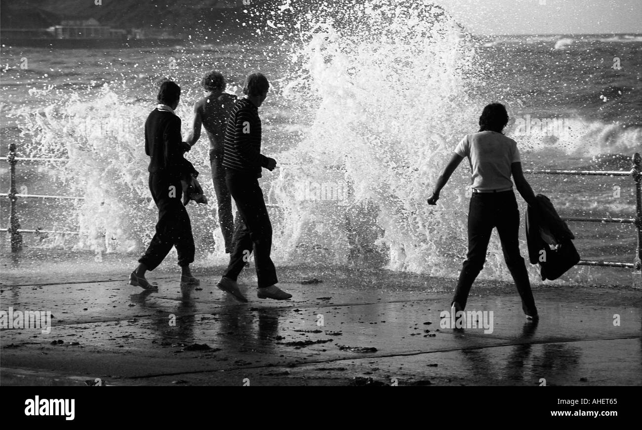 People dodging large waves on the sea front at Scarborough - Stock Image