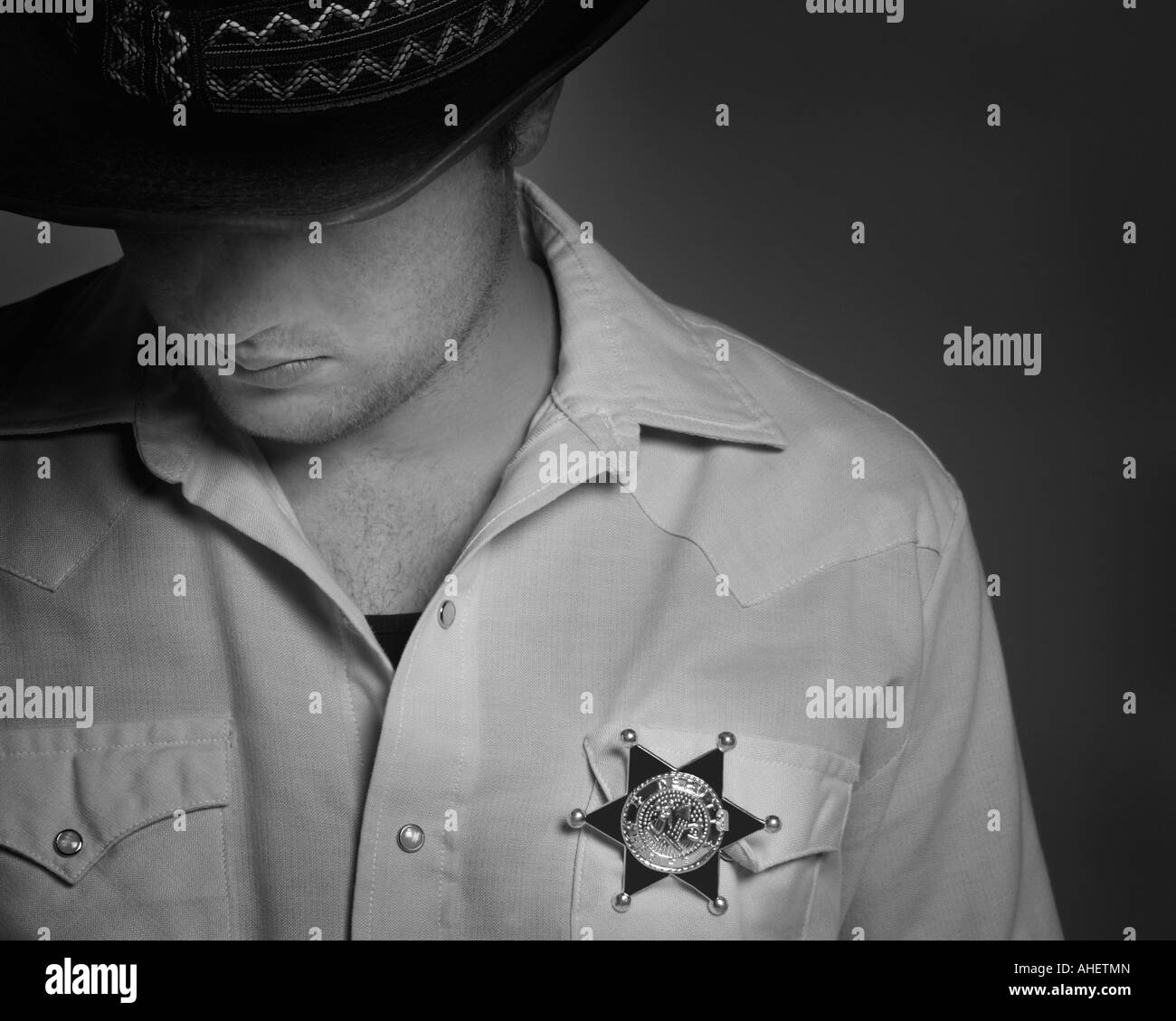 Cowboy looking down under hat with Sheriff's badge on shirt - Stock Image