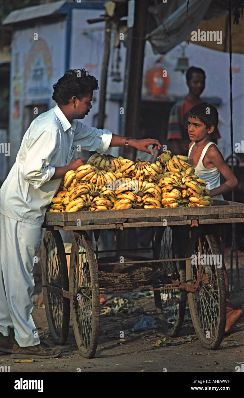 Buying bananas from a market stall Agra India - Stock Image